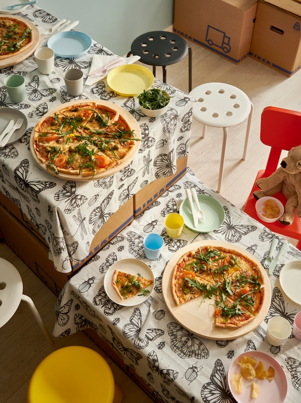 A makeshift table made of moving boxes and SOMMARMALVA shower curtain as tablecloth, set with pizzas on SNUDDA lazy Susans.