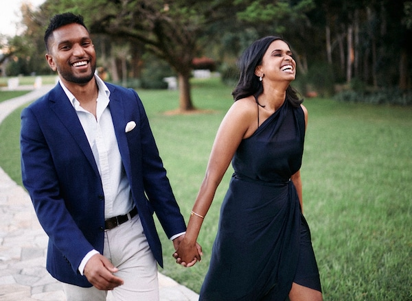 A man and a woman, both wearing formal clothing, are holding hands whilst walking. They are both laughing.
