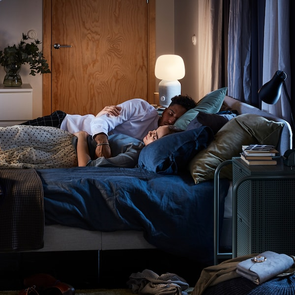 A man and a woman resting on a bed with dark blue PUDERVIVA bed linen, with a SYMFONSIK speaker lamp on a bedside table.