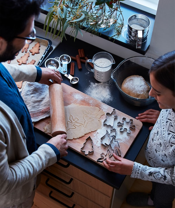 A man and a woman standing by a kitchen worktop that's littered with all the telltale signs of ongoing gingerbread baking.