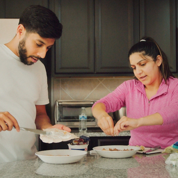 A man and a woman with one plate each are preparing breakfast in a kitchen with a stone worktop and grey cabinets.