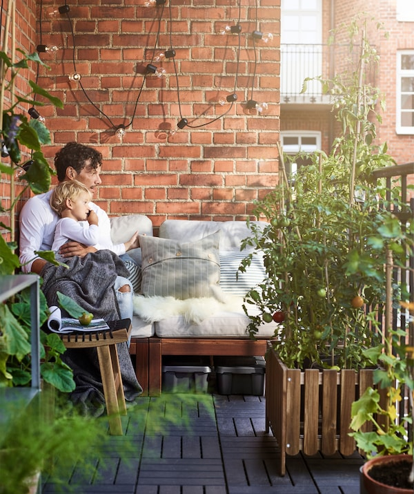 A man and child sitting on a sofa next to a red brick wall on a balcony, with many plants surrounding them.