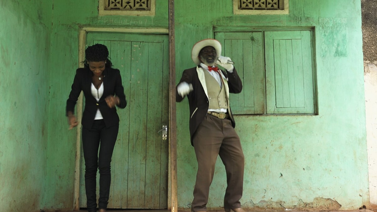 A man and woman dressed in smart clothes dancing in front of a green building.