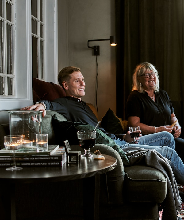 A man and woman on a green sofa with cushions and throws, drinks in glassware, tealights and books are on the coffee table.