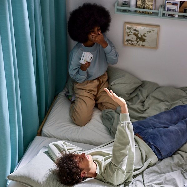 A man and woman on two beds with green/stripe BERGPALM and light grey/mélange SPJUTVIAL bed linen, beside a curtain.