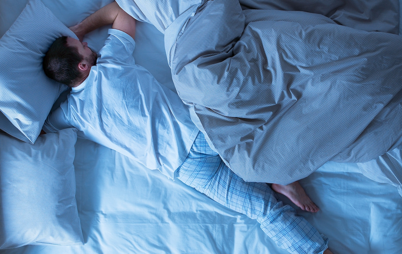 A man asleep with a duvet cover pushed to one side.