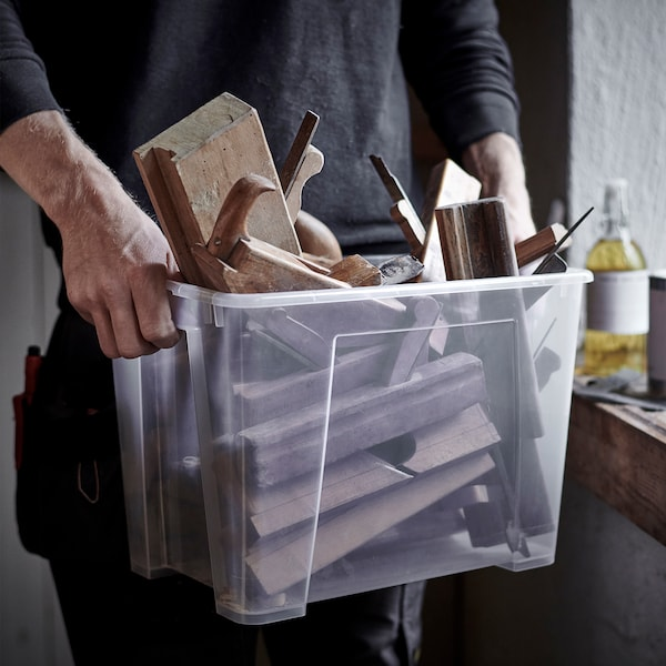 A man carrying a clear SORTERA plastic box filled with pieces of wood and wooden tools.