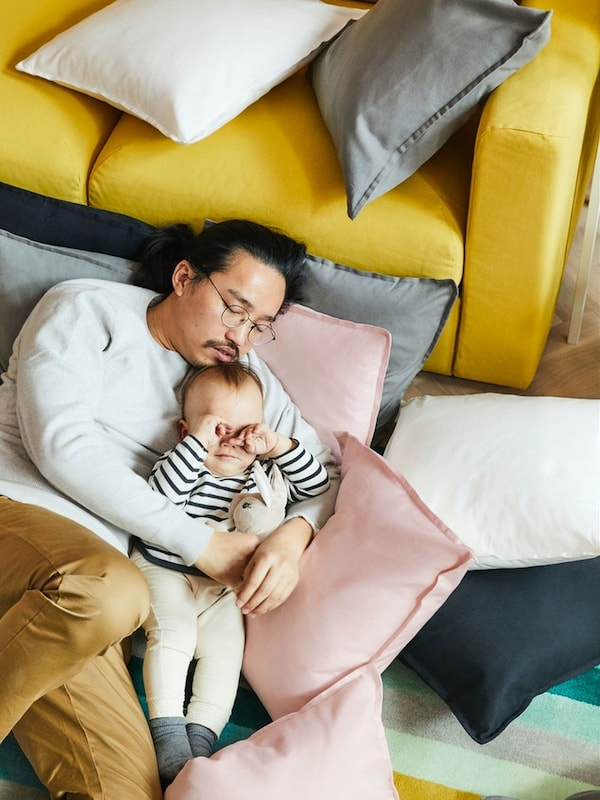 A man fell asleep holding his baby in his arms, and the baby is rubbing his eyes just about to fall asleep.