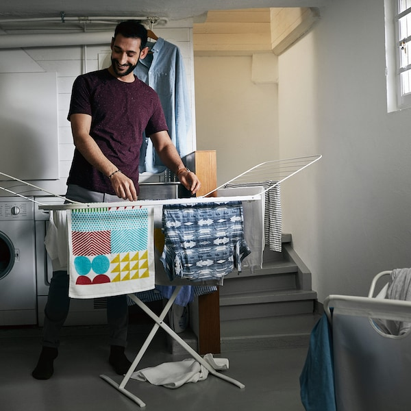 A man hanging laundry in the basement using the MULIG drying rack