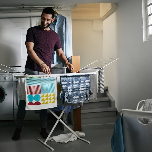 A man hanging t-shirts and towels in a basement room, on an IKEA MULIG drying rack.