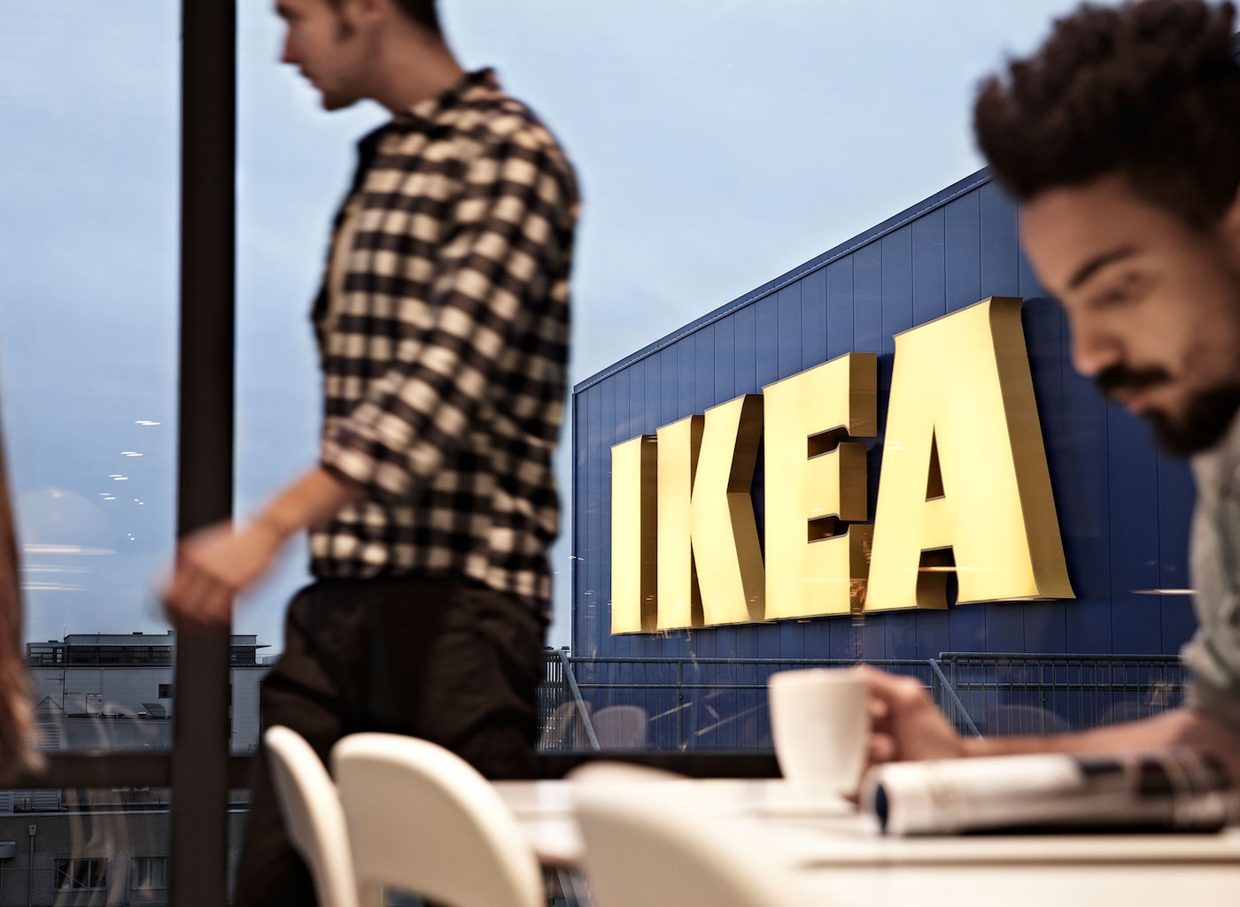 A man holding a mug of coffee with another man walking by, in front of the IKEA logo on a blue store.