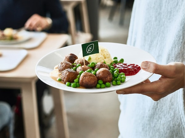 A man holding a plate of plant balls with mashed potato, peas, cream sauce and ligonberry jam.