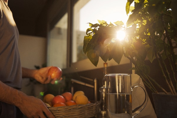 A man holds a basket of fruit on a balcony at sunset.