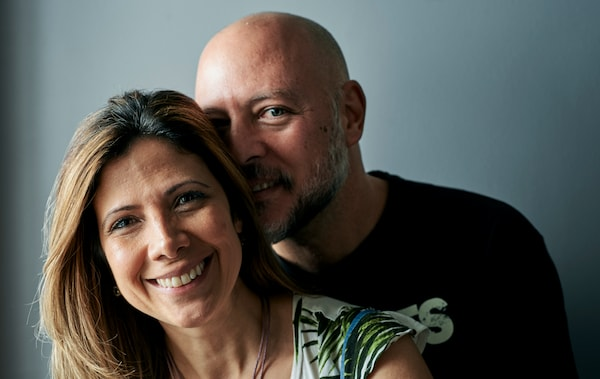 A man in a black T-shirt with a shaved head hugs a woman with brown highlighted hair.