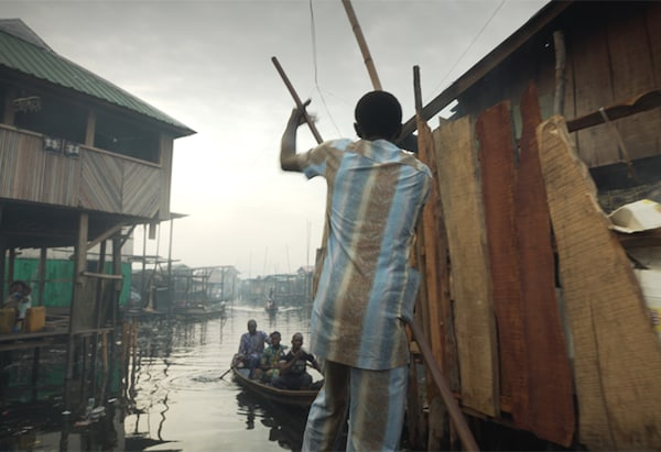 A man in a colourful suit punting on a boat through a floating wooden shanty town.