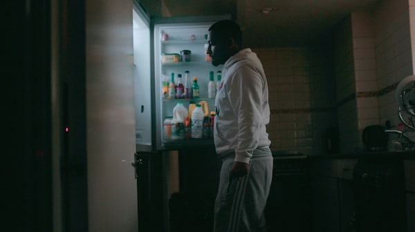 A man in a white hoodie and grey jogging pants is standing in a dark room, looking inside a fridge.