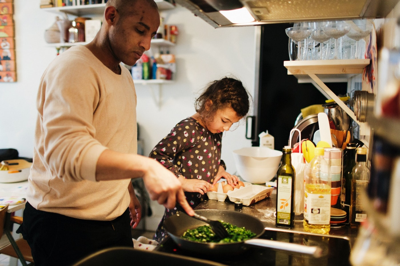 A man in a white sweater is frying vegetables in a pan with a spatula, and a child in a brown patterned sweater is in the kitchen is handling eggs in a carton.