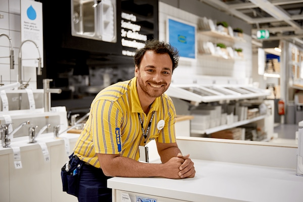 A man in a yellow IKEA uniform leaning on a countertop in an IKEA kitchen department smiling at the camera.
