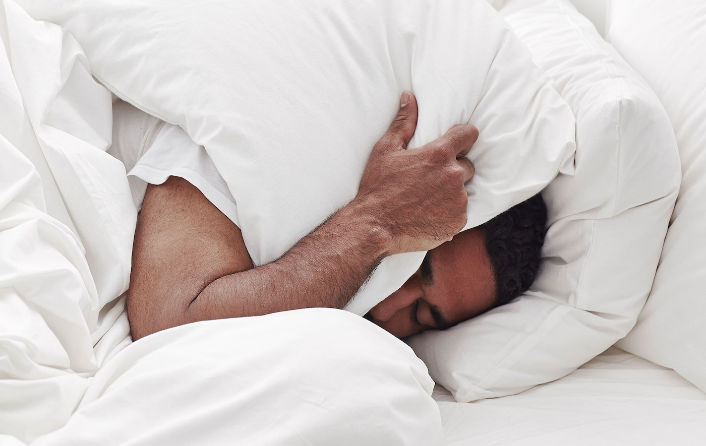 A man in bed covering his ears with a pillow.
