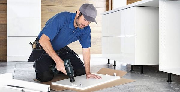 A man installing an IKEA kitchen