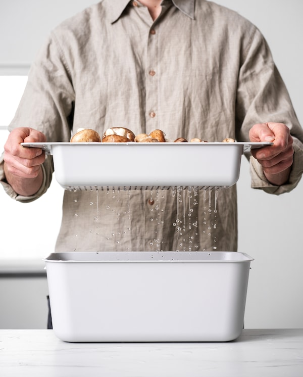 A man is holding a grey colander with mushrooms over a grey washing-up bowl. Water drips down into the washing-up bowl.
