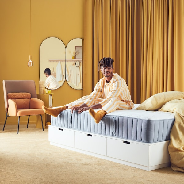 a man is sitting on a mattress and smiling