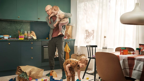 A man is standing in a kitchen with dark green fronts, holding a baby in his arms. He looks startled because the shopping bag has fallen over. A toddler picks up the things from the floor.