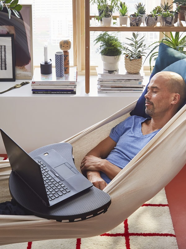 A man laying on a hammock with a laptop support on his lap
