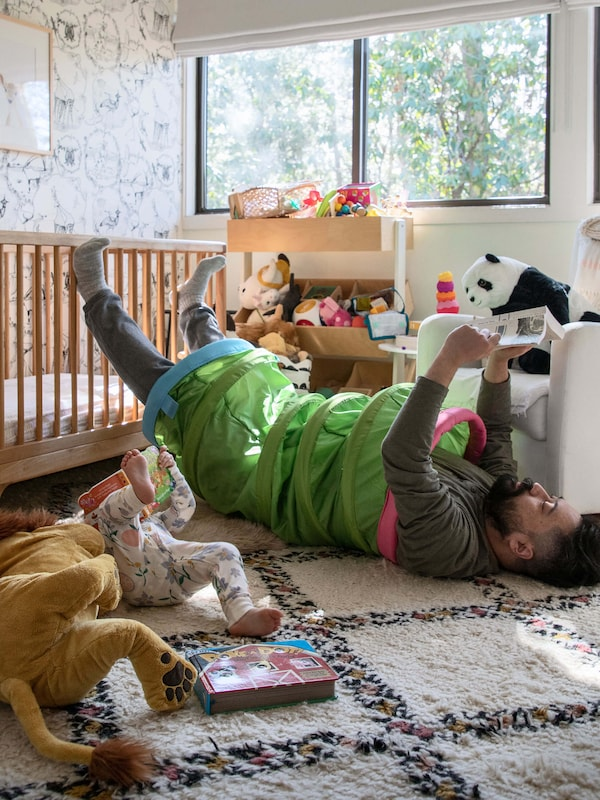 A man laying on the ground with a Play tunnel around his body and soft toys surrounding him.