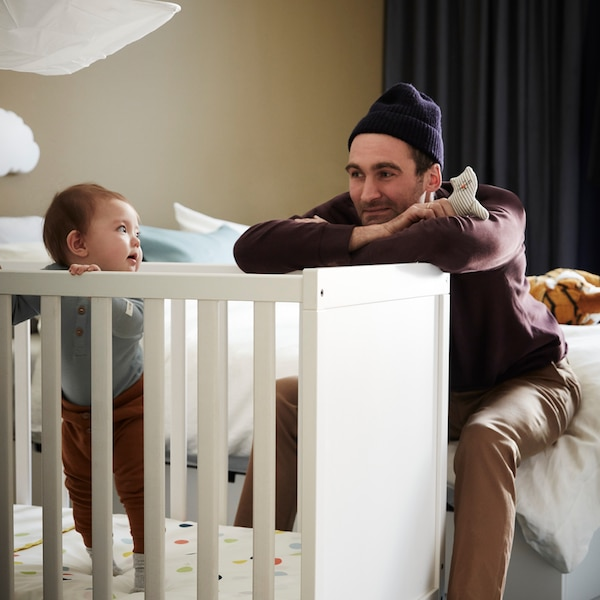 A man leaning against a white cot with a soft toy in his hand looking at a baby who is standing up inside the cot.