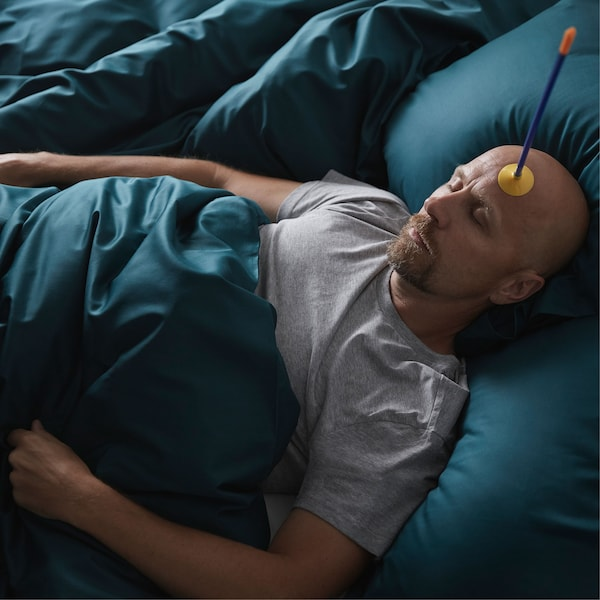 A man lies asleep in a plush-looking bed, with a toy suction-cup arrow stuck to his forehead.