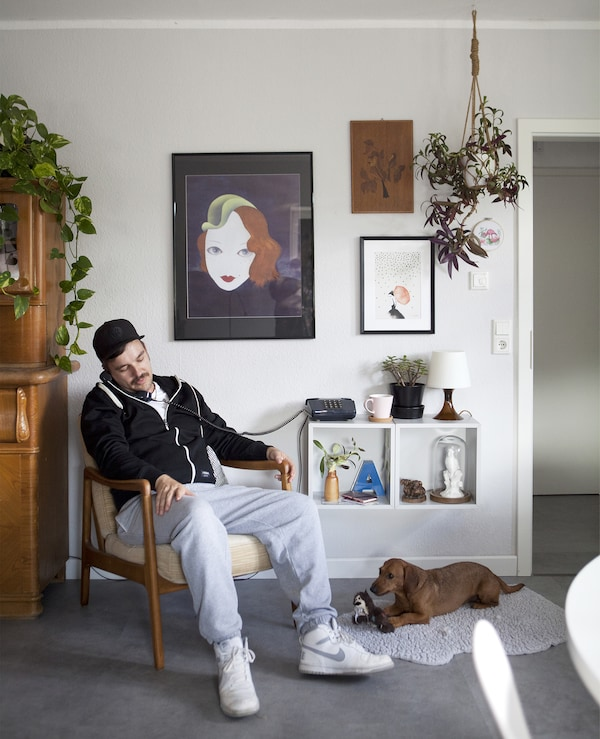 A man on the phone, sitting in a chair, with a dog on the floor by his feet.