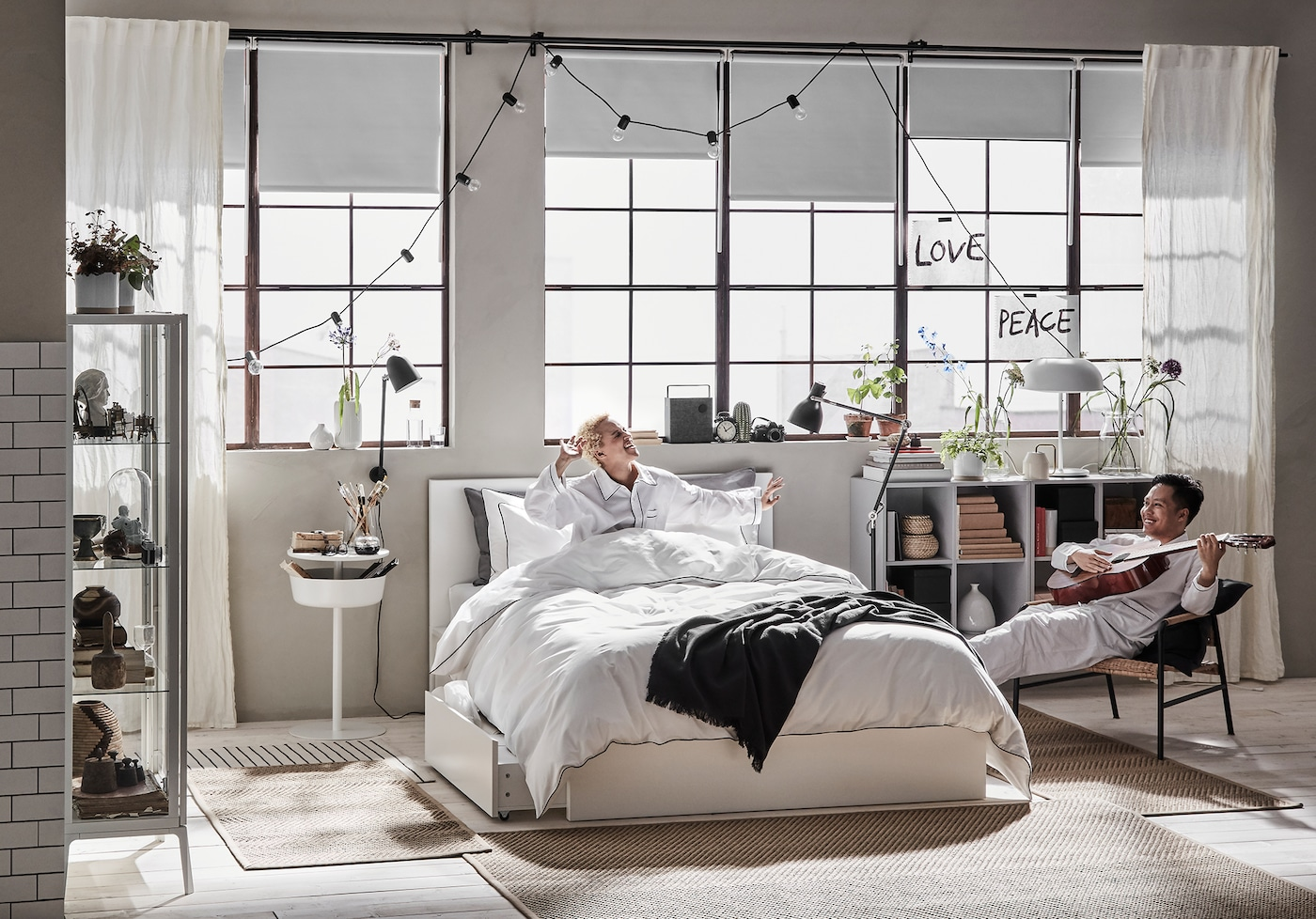 A man plays the guitar and a woman sings on the bed in an industrial loft.