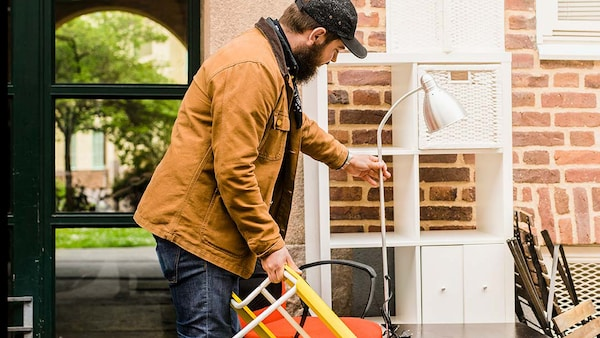 A man puts a lamp with other second-hand furniture in front of a house