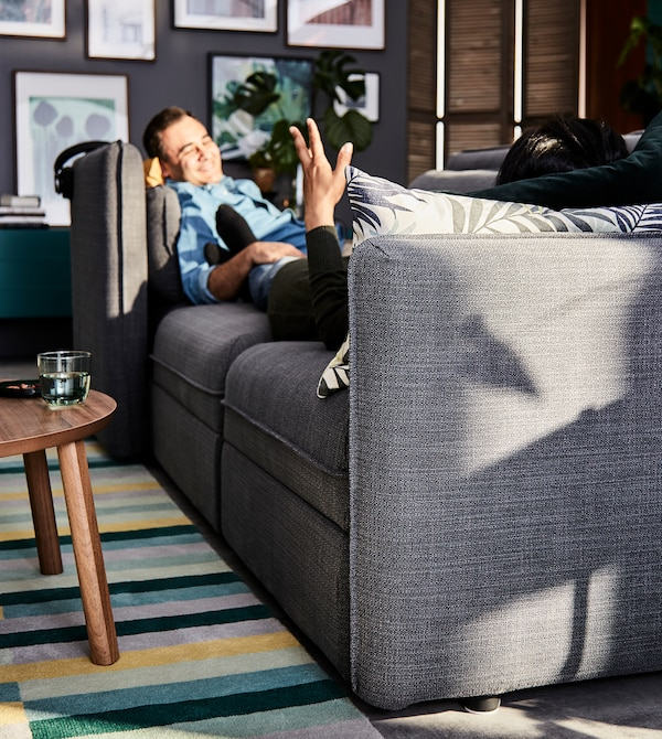 A man relaxing on a grey VALLENTUNA modular sofa, placed on a multi-coloured rug in a living room setting.
