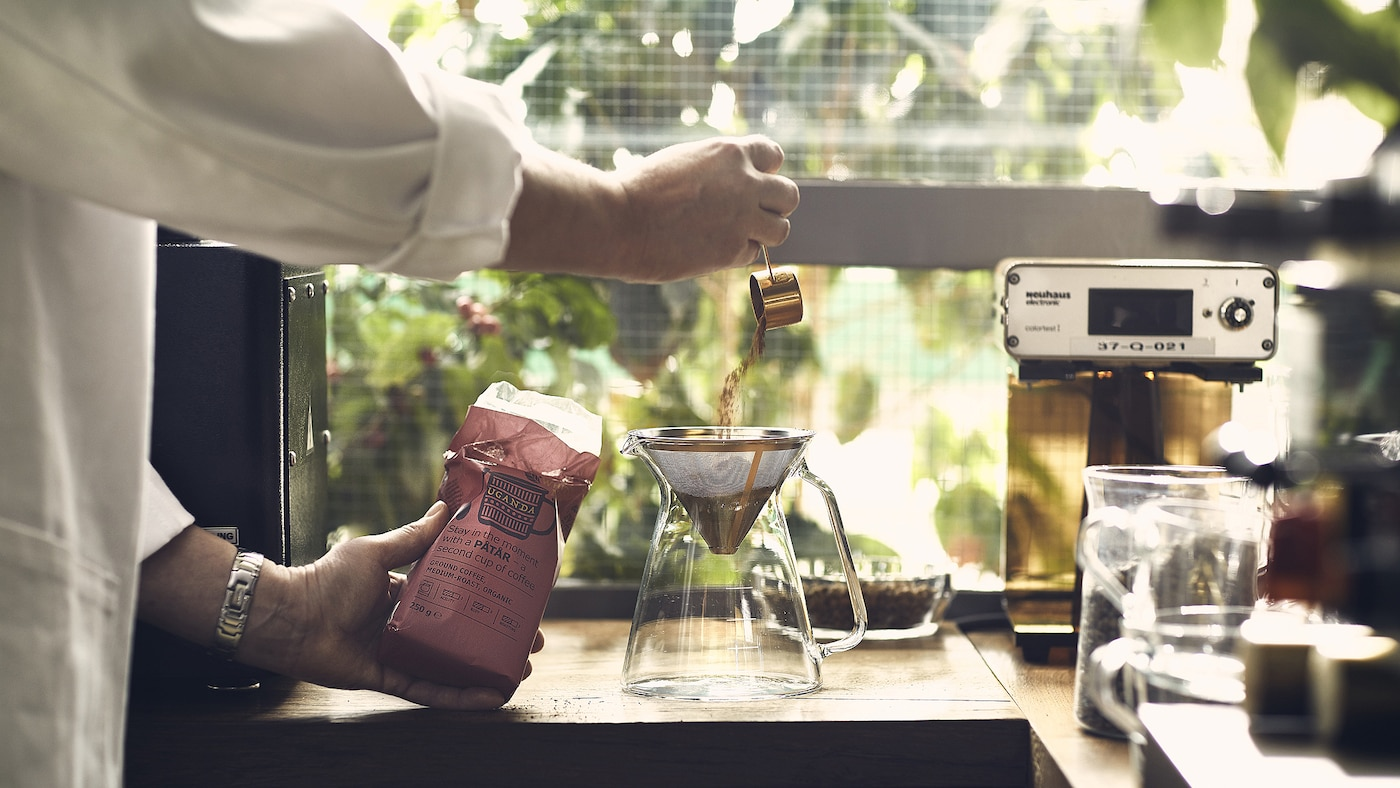 A man scoops coffee grounds into a filter inside a glass coffee pot next to a coffee machine on a kitchen counter top.