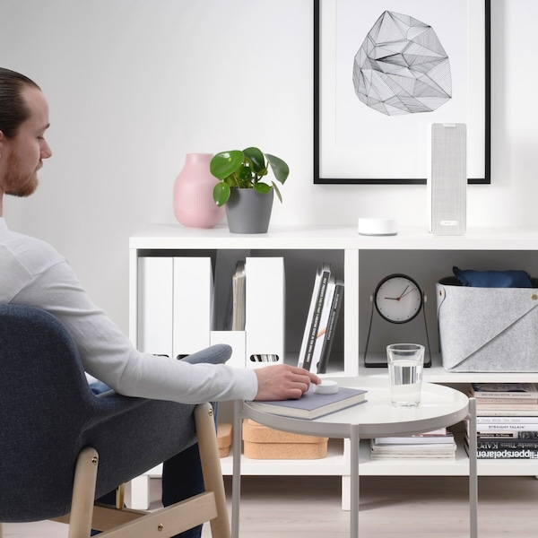 A man sitting down on a chair utilizing a smart home sound remote to control a SYMFONISK bookshelf speaker.