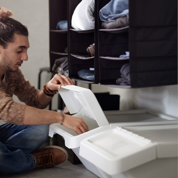 A man sitting on the floor, lifting the lid of a white plastic SORTERA box that is also placed on the floor.
