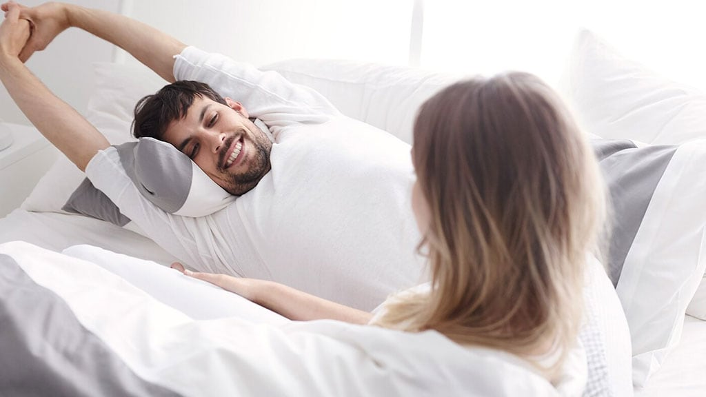 A man stretching in bed after a good night's sleep.