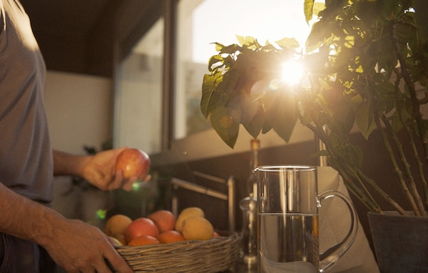 A man takes fresh fruit from a woven basket to wash it in the sink, while the sun peeks through a plant.