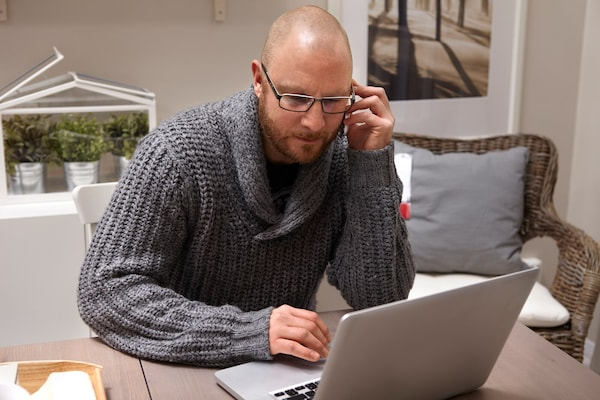 A man talking on the phone and working on a computer