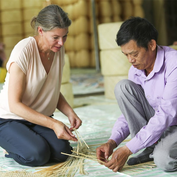 A man teaching traditional bamboo weaving techniques to Emma Olbers.