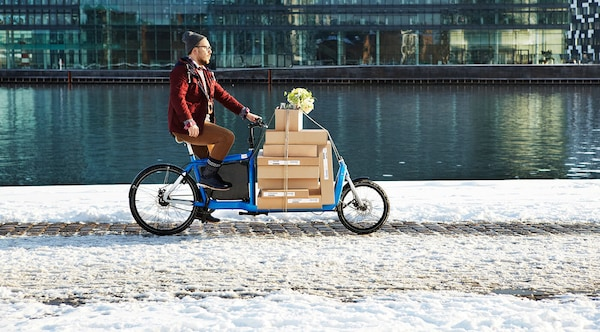 A man transporting IKEA boxes on a bicycle