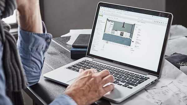 A man typing on laptop, looking at the IKEA online planner.