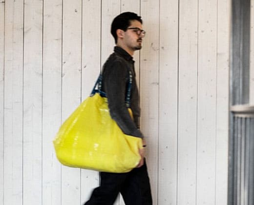A man walking with a yellow IKEA bag.