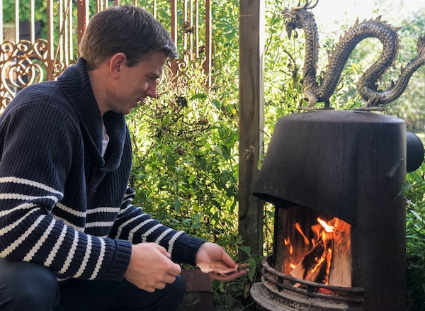 A man wearing a navy blue sweater with white stripes is busy making a fire in a fireplace.