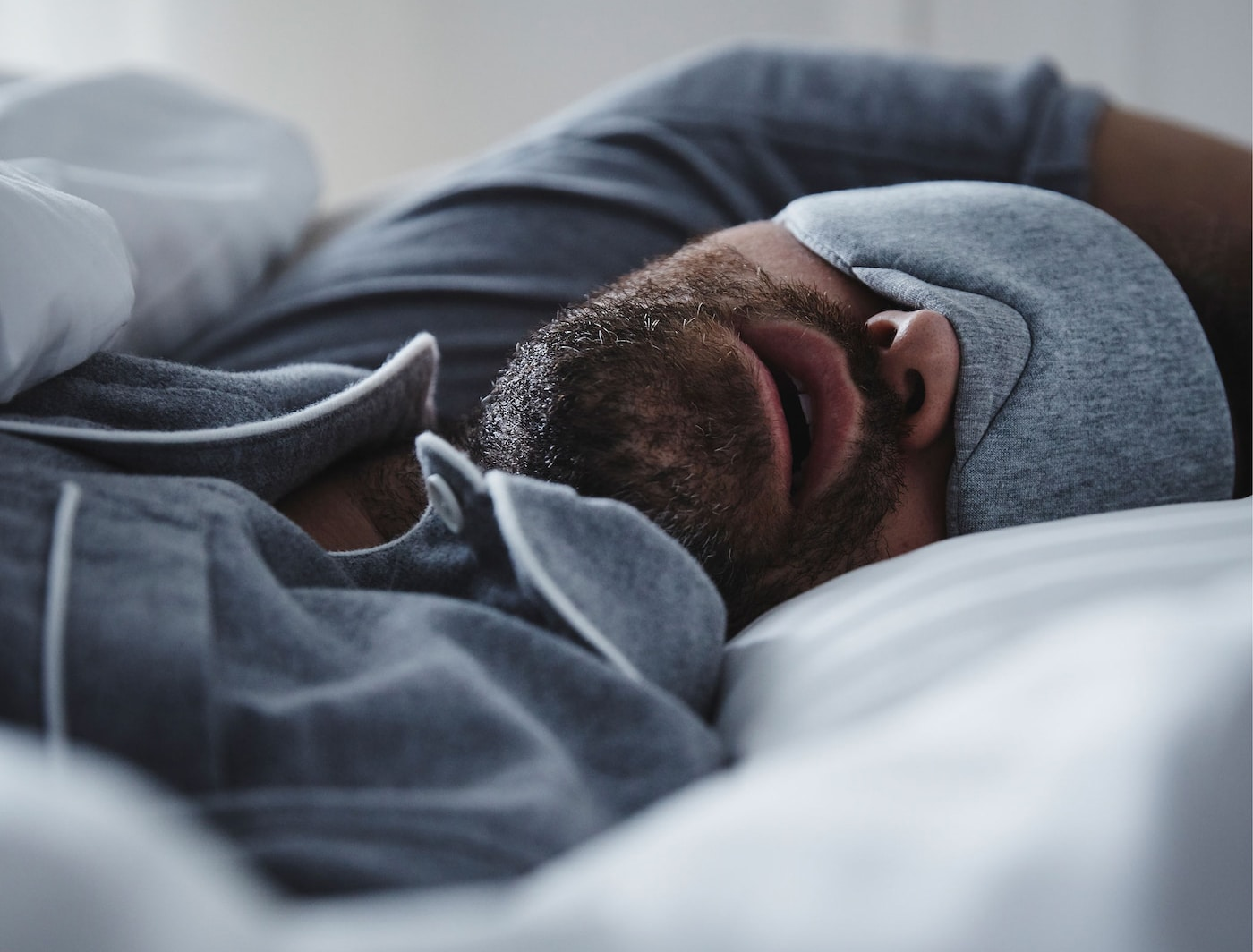 A man wearing blue pajamas and matching eye-mask lies asleep in bed.