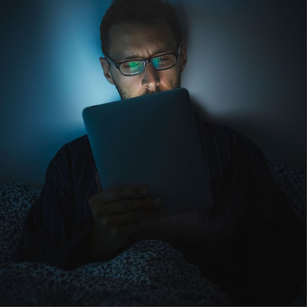 A man wearing glasses looks at an iPad in bed, its light reflecting on his tired-looking face.