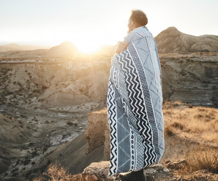 A man wearing pyjamas are standing outside to look sun rise