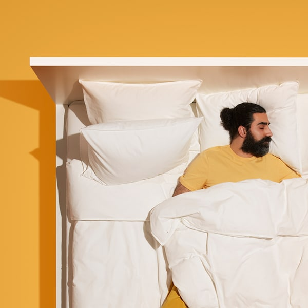 A man wearing yellow clothes sleeps in a white MALM bed with white bedding which stands on a dark yellow floor.